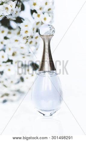 Perfume And White Flowers On A White Background