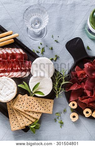 Cold Cuts And Cheese Are Served On A Tray On A Table With White Wine, Crackers, Grissini And Taralli