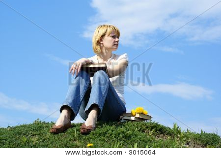 Female Student Outdoor On Green Grass With Books And Blue Sky