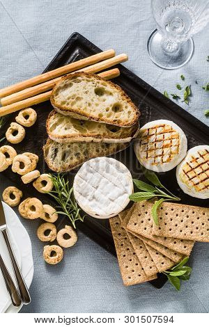 Grilled Italian Tomino Cheese Served On A Table With White Wine, Crackers, Grissini And Taralli With