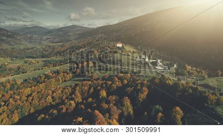 Autumn Forest Mountain Slope Village Aerial View. Panoramic Scenery Hill Meadow Landscape Sight. Wild Nature. Highland Scene of Building Clean Environment. Travel Concept Drone Flight