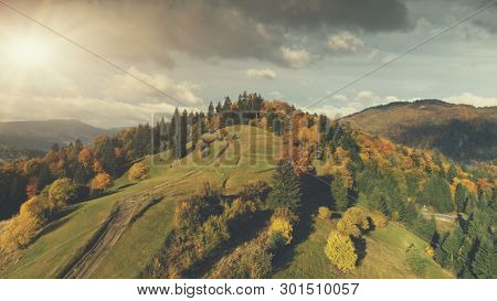 Majestic Autumn Mountain Landscape Aerial View. Nature Travel Beech Tree Forest Hill Dirt Road Overview. Scenic Colorful Mountainous Range Dark Grey Cloud Overcast Sky Drone Shot