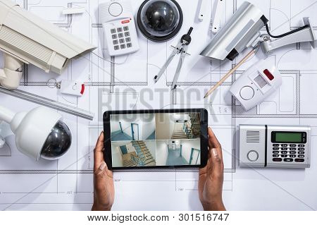 An Elevated View Of Person Watching Footage On Digital Tablet With Security Equipment On Blueprint poster