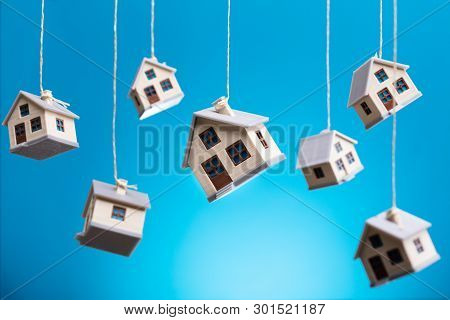 Miniature Houses Hanging By Strings Against Blue Background