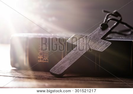 Wooden Christian Cross On Holy Bible Over Wooden Table
