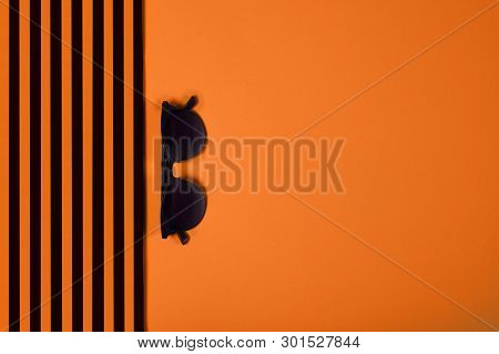 Summer And Vacation Concept. Top View Of Striped Clothes And Sunglasses On Trendy Russet  Orange Col