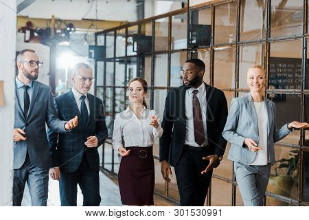 multicultural group of handsome businessmen and happy businesswomen walking in office poster