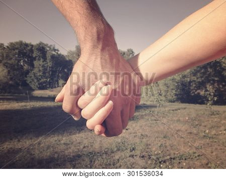 A Male Hand Holds A Female Hand Against A Background Of Nature. Couple On A Walk Holding Hands, The