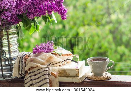 Book, Glasses, Cup Of Tea And Lilac On A Wooden Window. Fragrant Tea In The Garden. Romantic Concept