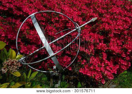 Metal Globe Garden Decoration With Pink Flower Bush Background