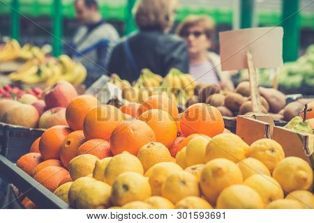 Shopping Fruit On The Marketplace. Orange And Lemon In Baskets Ready For Sale On The Marketplace In