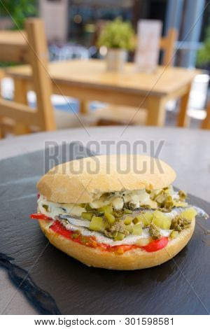 Anchovies sandwich with pepper and gherkins.
