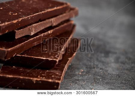 Dark chocolate bar pieces closeup. Sweet food photo concept. The chunks of broken chocolate stacked on grey background.