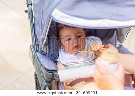 Happy Baby Boy Is Eating While Sitting In A Baby Carriage Outdoor