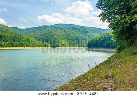 Water Storage Reservoir In Mountains. Beautiful Nature Scenery In Summer. Forest On The Shore Around