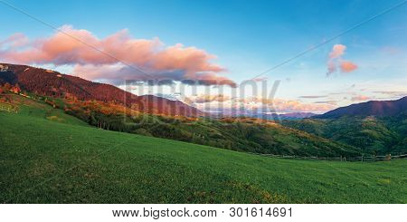 Beautiful Rural Panorama In Mountains At Sunset. Agricultural Fields On Hills. Ridge In The Distance