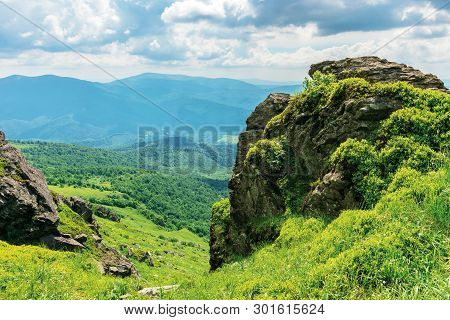 Summer Nature Landscape In Mountains. Huge Boulders On The Edge Of A Grassy Slope. Ridge Behind The