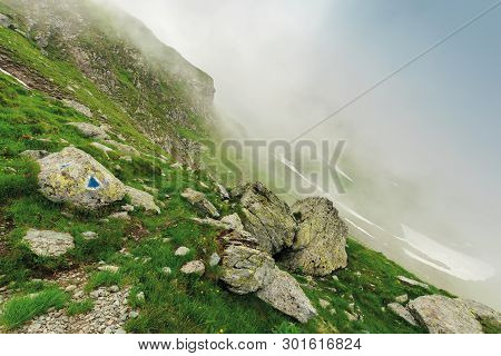 Hiking Uphill In The Fog. Huge Boulders On A Grassy Slope. Mysterious Nature Scenery. Bad Weather Co