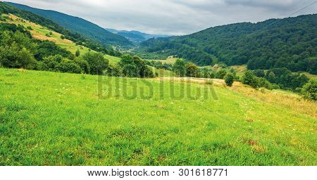 Countryside In Mountain On A Cloudy Summer Day. Settlement In The Distant Valley. Beautiful Landscap