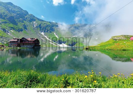 Beautiful Summer Scenery Around Balea Lake. Grassy Meadows And Low Clouds Around. Popular Travel Des