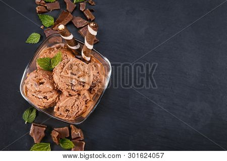 Scoops Chocolate Ice Cream In Glass Bowl With Wafer Sticks, Cone And Chocolate On A Black Slate Boar