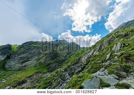 Hiking Uphill Rocky Slopes Of Fagaras Mountains. Hard Path Among Big And Sharp Boulders. Sunny Summe