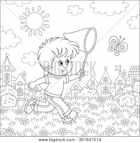 Little Boy Running And Catching A Flying Butterfly With A Butterfly Net Among Flowers On A Sunny Sum