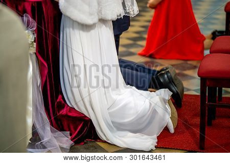 Bride And Groom Preparing For Communion On Knees At Wedding Ceremony In Church. Bride And Groom Duri