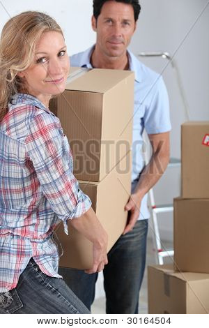 Couple moving in carrying cartons
