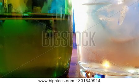 Close Up Of An Ice Cold Green Bottle Of Drink Next To A Frosted Ice Cold Glass