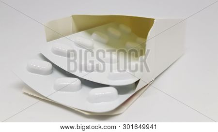 2 Strips Of Sealed Tablets Sticking Out Of A Box.