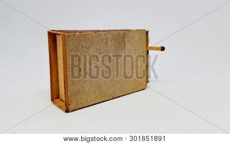 An Old Worn Matchbox With A Safety Match Sticking Out.