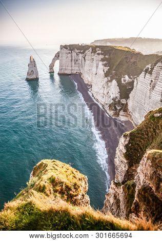 coastal landscape along the Falaise d'Aval the famous white cliffs of Etretat village, with the Porte d'Aval natural arch and the rock known as the Aiguille d'Etretat, Normandie, France