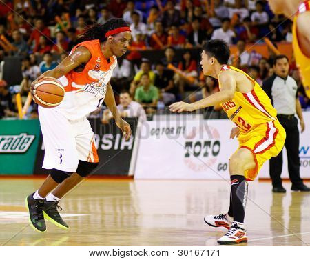 KUALA LUMPUR - FEBRUARY 19: Malaysian Dragons' Tiras Wade (white) dribbles in at the ASEAN Basketball League match against Singapore Slingers on Feb 19, 2012 in Kuala Lumpur, Malaysia.  Dragons won 86-71.