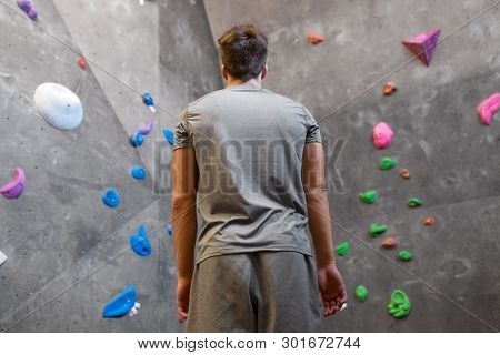 fitness, extreme sport, bouldering, people and healthy lifestyle concept - young man at indoor climbing wall in gym from back