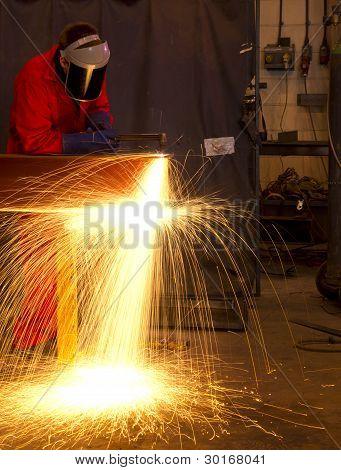 Schweißer-Kurven zu schneiden Metall Strahl mit orange Funken.