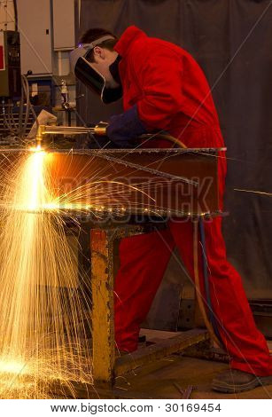 Welder In Red Overalls Cuts Metal.
