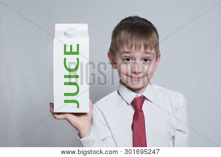 Little Blond Boy Holds And Shows A Big White Carton Juice Package. White Shirt And Red Tie. Light Ba