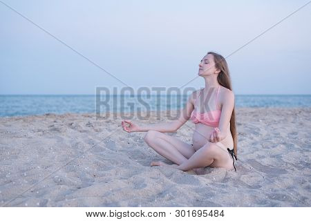 Pregnant Woman Sitting On A Beach And Meditates. Soft Evening Light, Deserted Beach.