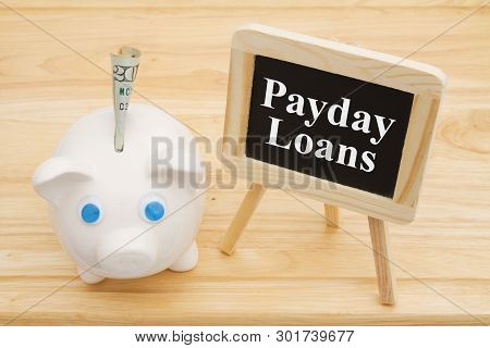 Learning About Payday Loans, A Piggy Bank With Money On A Desk With Chalkboard With Text Payday Loan