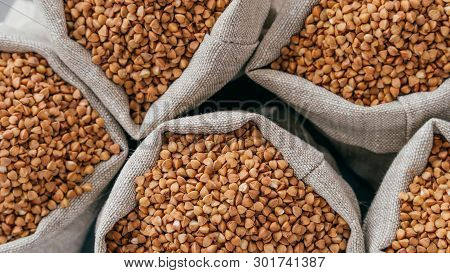 Food And Healthy Eating Concept. Close Up Shot Of Raw Buckwheat In Sacks. Nurture. Dry Healthy Cerea