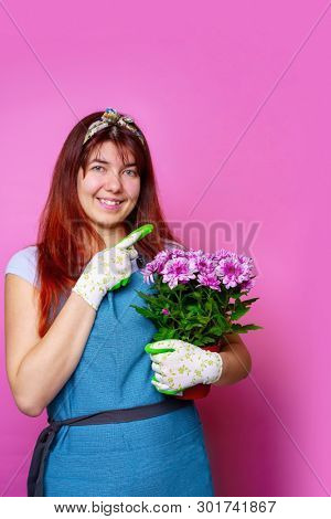 Photo of cheerful woman with chrysanthemum pointing hand to side