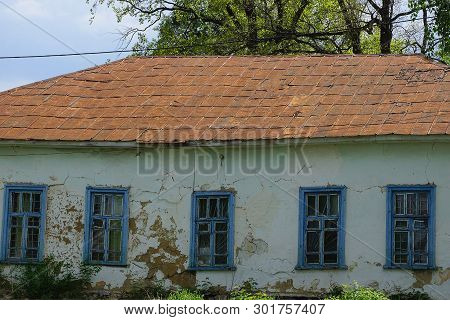 Facade Of A Gray Rural Old House With Blue Windows And A Brown Iron Roof