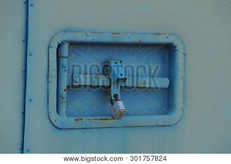 Padlock And Latch On The Old Blue Gray Iron Wall