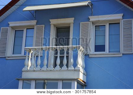 Open White Concrete Balcony With Door And Windows With Wooden Shutters On The Blue Wall