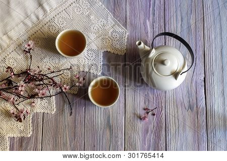 White, Chinese Set With Tea And Blossoming Branch On A Wooden Table Close-up