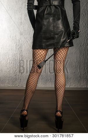 The Dominant Woman In A Leather Dress With A Spank In Her Hand Back. Bdsm Outfit- Image