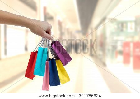 Crop Female Hand Holding Colorful Paper Bags On Background Of Shopping Center.