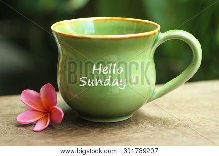 Green Ceramic Cup Of Coffee With Hello Sunday Greetings On It And Beautiful Pink Balinese Frangipani