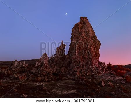 Unearthly scenery with bizarre rock formations and crescent moon poster